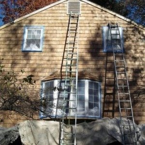 Taped off window and covered landscaping during exterior house painting